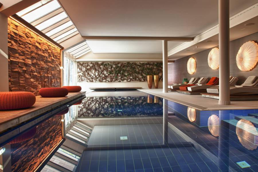 Indoor-Pool with sunbeads and poufs Strandhotel am Weissensee