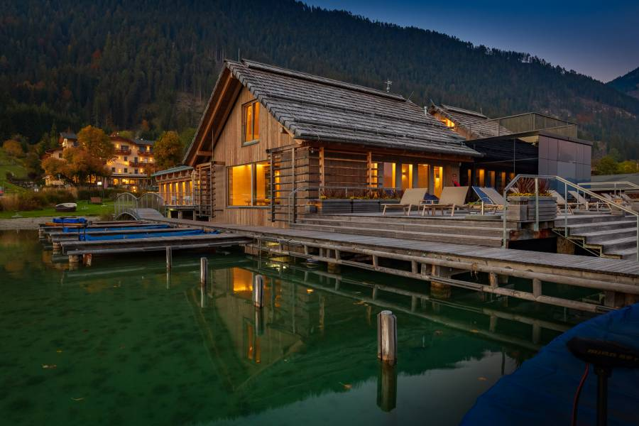 External view of the illuminated lake-spa in the evening  Strandhotel am Weissensee