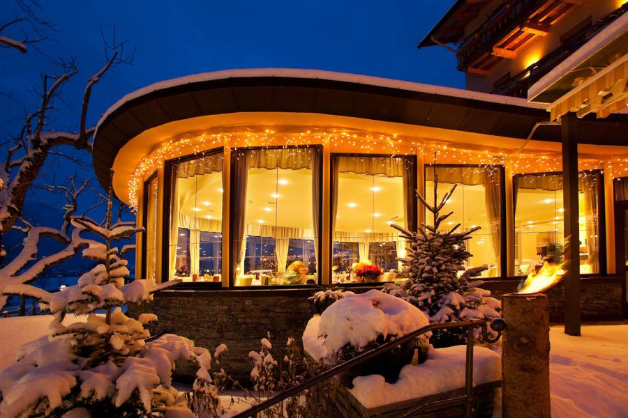 External view of the illuminated restaurant at night Strandhotel am Weissensee
