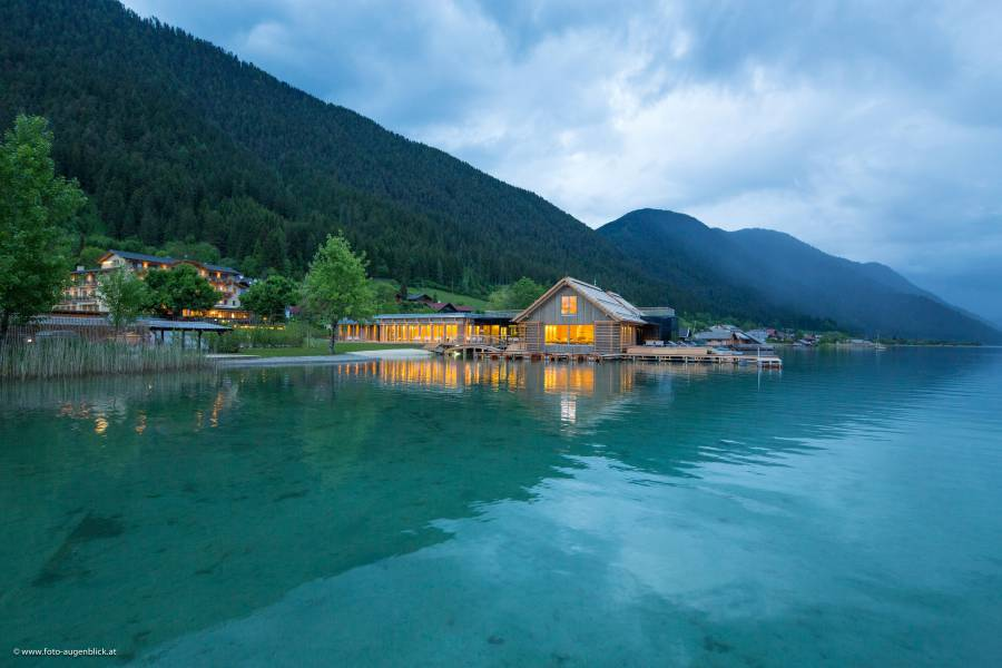 Illuminated external evening view of the lake-spa Strandhotel am Weissensee